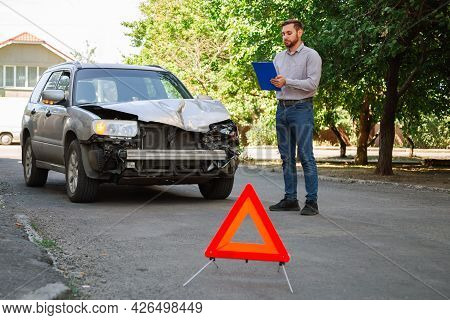 Insurer Inspects Car And Calculates Damage After Car Accident. Man Auto Insurance Agent Inspect Vehi