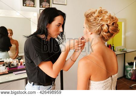 Professional Female Makeup Artist Applying Cosmetics On Model Face Use Brush Working At Beauty Salon