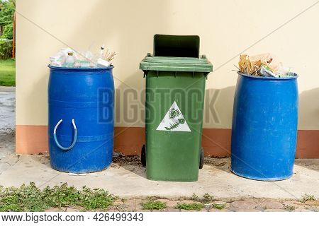 Overflowing Garbage Bins With Household Waste In City. Blue And Green Bins To Conserve The Environme