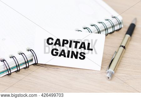Text Capital Gains On White Card Next To Notebook And Pen On Wooden Table