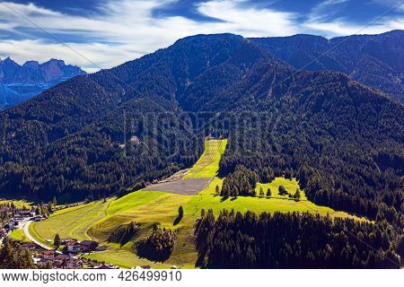 Village of Santa Maddalena. Magnificent Dolomites on a sunny autumn day. Europe, Val de Funes. The ski slope is overgrown with grass.  Tyrol, Italy