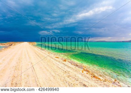 Low winter clouds are reflected in the green sea water. The landfill embankment runs through the sea. Winter thunderstorm begins. Israel. The picturesque Dead Sea.