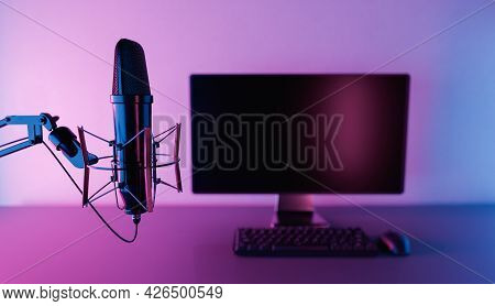 Close Up Of Studio Microphone With Out Of Focus Pc Monitor With Neon Lighting. Concept Of Podcast, R