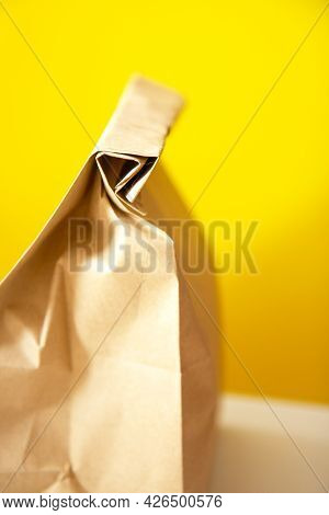 Brown Craft Paper Bag On Yellow Background. Recycled Paper Shopping Bag, Lunch Bag