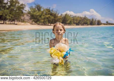 Boy Collects Packages From The Beautiful Turquoise Sea. Paradise Beach Pollution. Problem Of Spilled