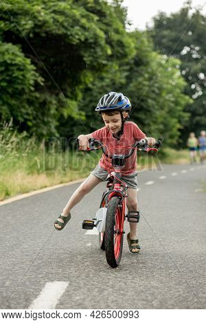 Child Riding Bicycle On The Bike Path At Rain. Kid In Helmet Learning To Ride At Summer. Happy Boy R