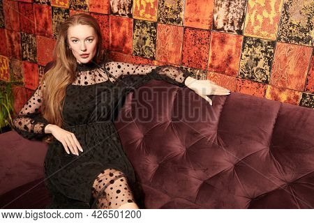 Glamorous lifestyle. Beautiful young woman in black evening dress sits on a velvet sofa in luxury apartments. Beauty, fashion. Modern interior, furniture.