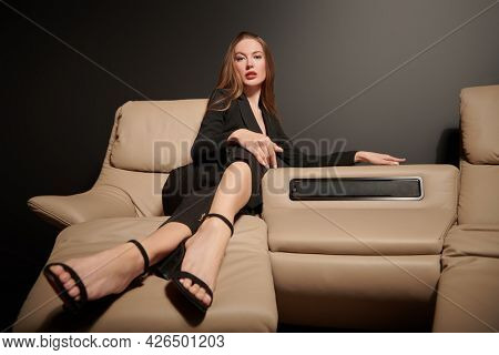 Elegant business woman in black pant suit lies on a leather sofa in modern apartments. Fashion. Modern interior, furniture.