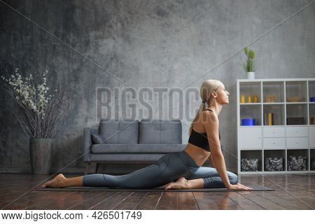 Young and sporty girl in sportswear is doing exercises in home interior. Fit and slender blond woman goes in for sports and fitness. Healthcare, fat burn and wellness.