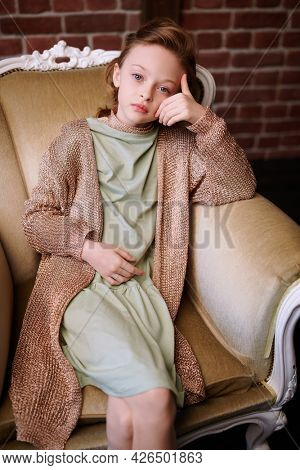 Kid's fashion. Portrait of a cute eight year old modern girl sitting in a vintage armchair in loft room.