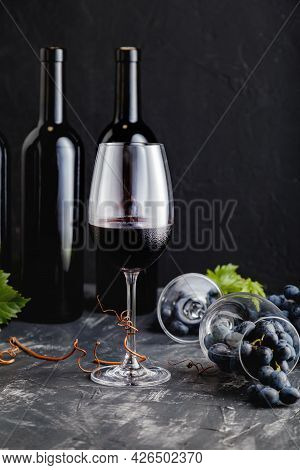 Wine Composition On Black Stone Table. Red Wine Bottles, Grape Bunches With Leaves And Vines On Dark