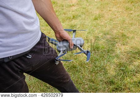 Man Holding Grey Drone Outside In The Park.
