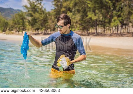 Man Collects Packages From The Beautiful Turquoise Sea. Paradise Beach Pollution. Problem Of Spilled