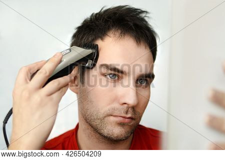 Handsome Man Cutting His Own Hair With A Clipper And Looks In The Mirror. Self-care In The Condition