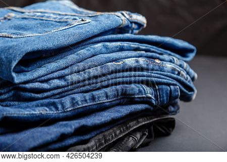 Blue Jeans Trousers Stack Textile Texture Fabric Background. Stack Of Variety Blue Color Jeans, Deni