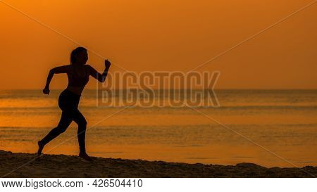 Silhouette Athletic Woman Jogging Exercise And Relax And Freedom On Sand Beach. People Running And W