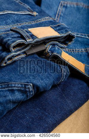 Stack Of Variety Blue Jeans, Denim Jean Textiles As Background. Different Blue Jeans Trousers Stack