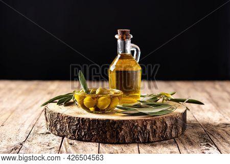 Virgin Olive Oil Bottle And Green Olives On Wooden Table