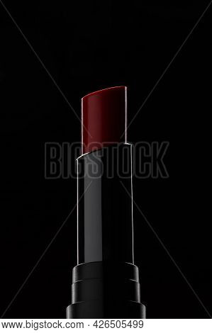 Close-up Of Red Lipstick With Shadow On Black Background. Modern Make-up Concept