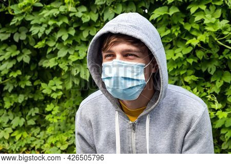 Young Man In The Flu Mask On The Green Leaves Background