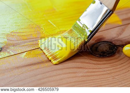 An Artist Paints Wooden Boards With A Brush With Synthetic Bristles With Acrylic Yellow Paint Close-