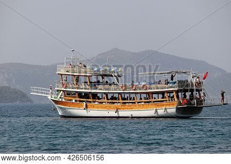 Hisaronu, Turkey - July 2021: Boat With Tourists Sailing In Aegean Sea On Misty Mountains Backgrou