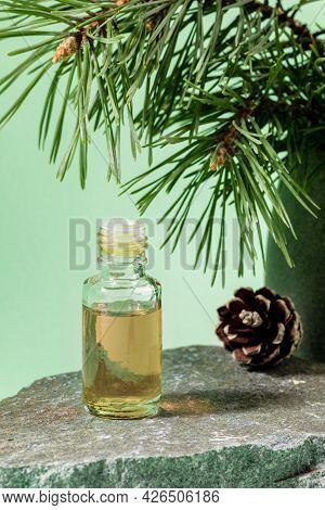 Essential Pine Oil In Glass Bottle On Grey Stone Granite On Mint Green. Vertical Orientation.