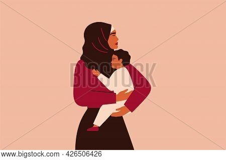 Arabian Woman In Hijab Holds Her Baby With Love And Care. Strong Muslim Mother Cuddles Her Child And