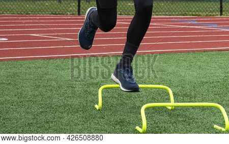 Front View Of A Male Runner Jumping Over Yellow Mini Hurdles On One Leg On A Turf Field.
