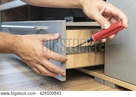 Young Handyman In Overall Installing Drawer In Kitchen. The Man Adjusts The Drawer. Self-assembly Of