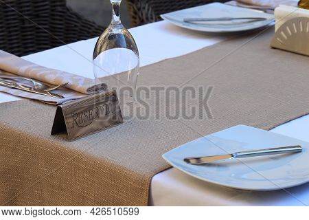 Restaurant Reserved Table Sign With Wineglasses And Plates.
