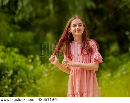 Portrait Of A Girl In A Pink Dress. Outdoors. Lifestyle And Happiness Concept.