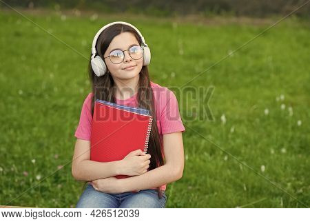 Audio To Rock Your Life. Small Child Listen To Music On Green Grass. Little Girl Wear Audio Headphon