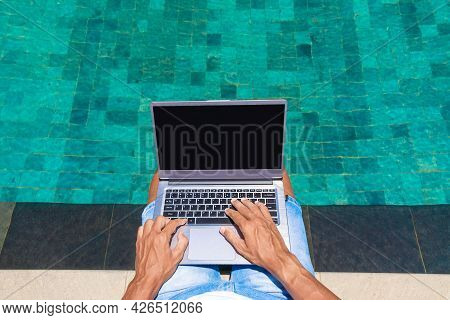 A Man Works On A Laptop By The Pool. Freelance, Work In Nature. Hands Are Typing Text.