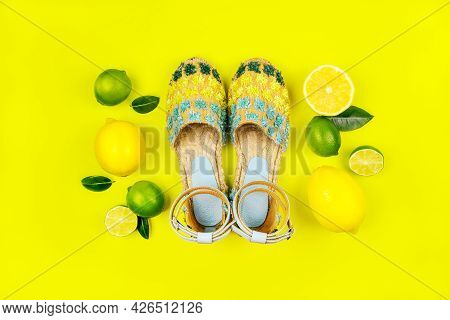 Summer Fashion Flatlay With Espadrilles Sandals, Lemons And Lime Isolated On Yellow Background.