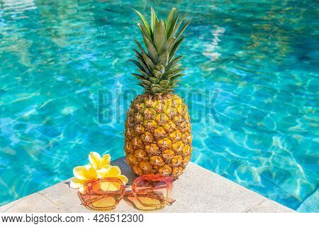 Juicy Pineapple And Glasses By The Pool. Summer Concept.