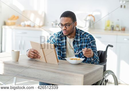 Millennial Handicapped Black Man In Wheelchair Eating Breakfast And Reading Book Indoors