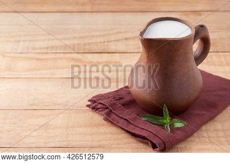 Clay Jug Of Organic Kefir, Yogurt Or Ayran On Wooden Table, Space For Text. Homemade Fermented Dairy