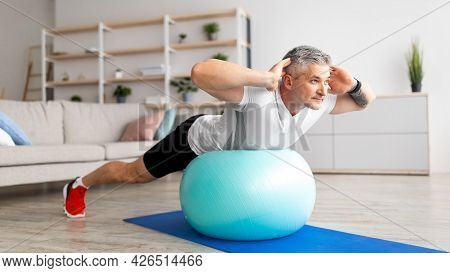 Sporty Mature Man Doing Exercises With Fitness Ball At Home, Working Out His Back Muscles, Panorama,