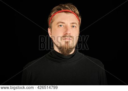 Funny Bearded Man With Red Headband, Black Background. Young Guy In Black Polo Neck Sweater. Ironic