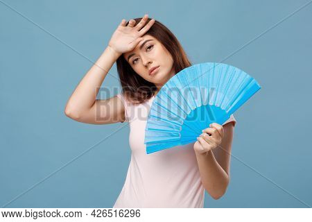 Tired Young Lady With Fan Touching Her Sweaty Head