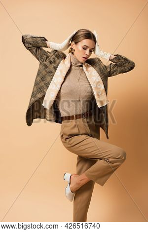 Trendy Woman In Blazer And Trousers Holding Hands Near Head While Standing On One Leg On Beige