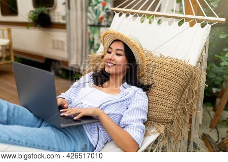 Lovely Asian Woman Using Laptop Pc While Lying In Hammock Near Motorhome On Camping Trip