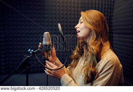 Female singer sings a song, recording studio