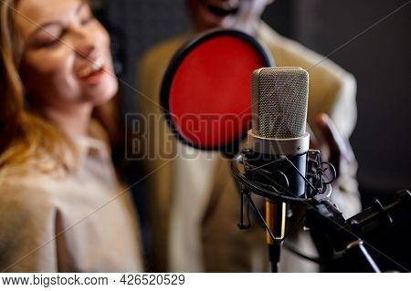 Male and female singers sings, recording studio