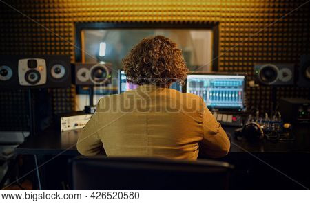 Male sound engineer at mixing consol, back view