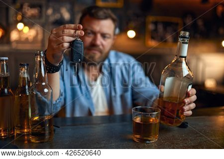 Drunk man with car key sitting at counter in bar