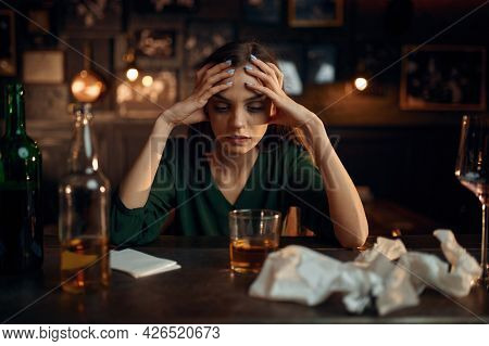 Drunk depressed woman at the counter in bar