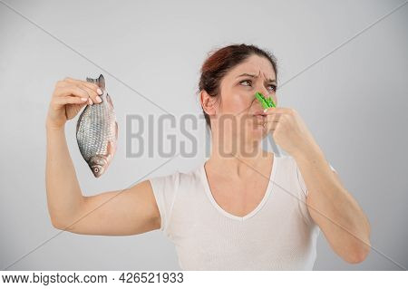Caucasian Woman With A Clothespin On Her Nose Because Of The Disgusting Smell Of Fish. A Metaphor Fo