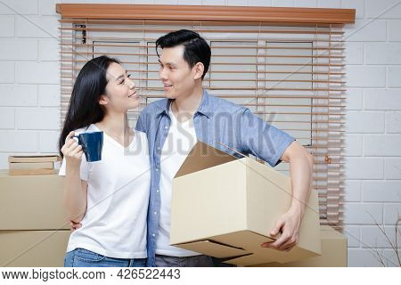Asian Couple Moving Into A New Home There Were Many Large Brown Cardboard Boxes Placed In The Room.